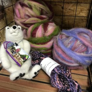 Purple and green wool sits beside a wool felted polar bear