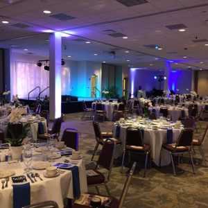 Round banquet tables with a stage and blue uplighting