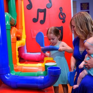 A little girl plays a pipe organ while her mother and baby sibling watch on at Buckeye Children's Museum