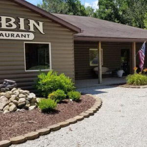 A green sided building with a sign that reads Cabin Restaurant