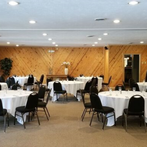 Private event room with wood paneled walls and tables with white tablecloths