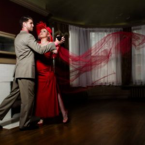 A woman in red dances with a man