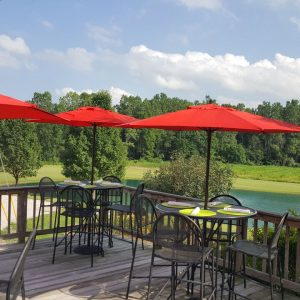 Patio deck with seating under bright red umbrellas