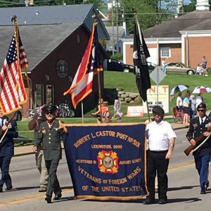 Veterans march in a parade carrying a VFW flag between them