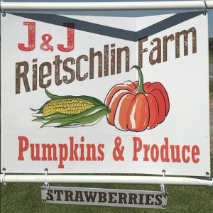 White sign reads J & J Rietschlin Farm with an ear of corn and a pumpkin pictured below