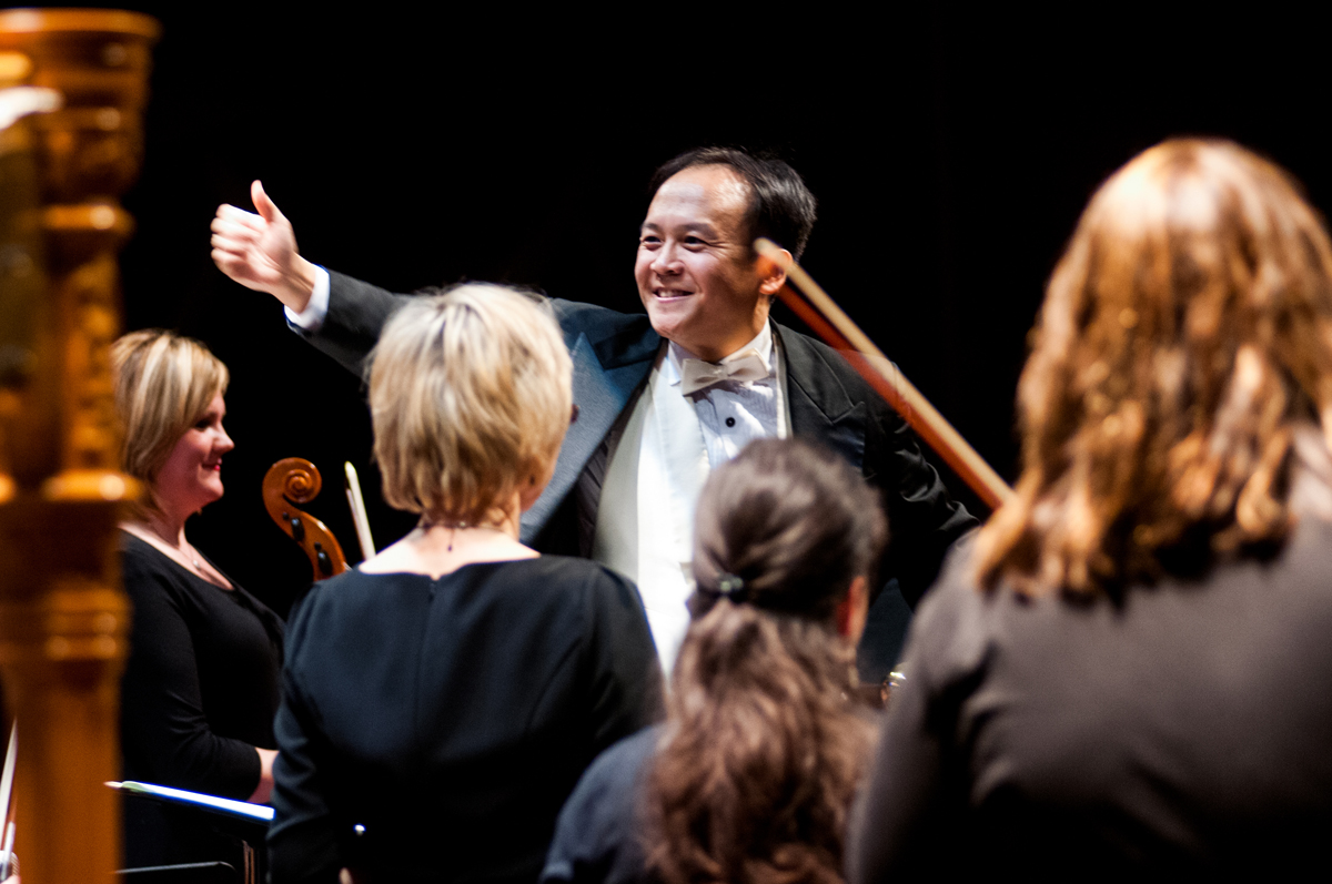 Holiday Events - A man in a black tuxedo gestures to four orchestra players