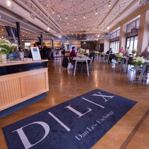 View of the hostess stand with a large rug that reads DLX at the entrance to Cafe on Main