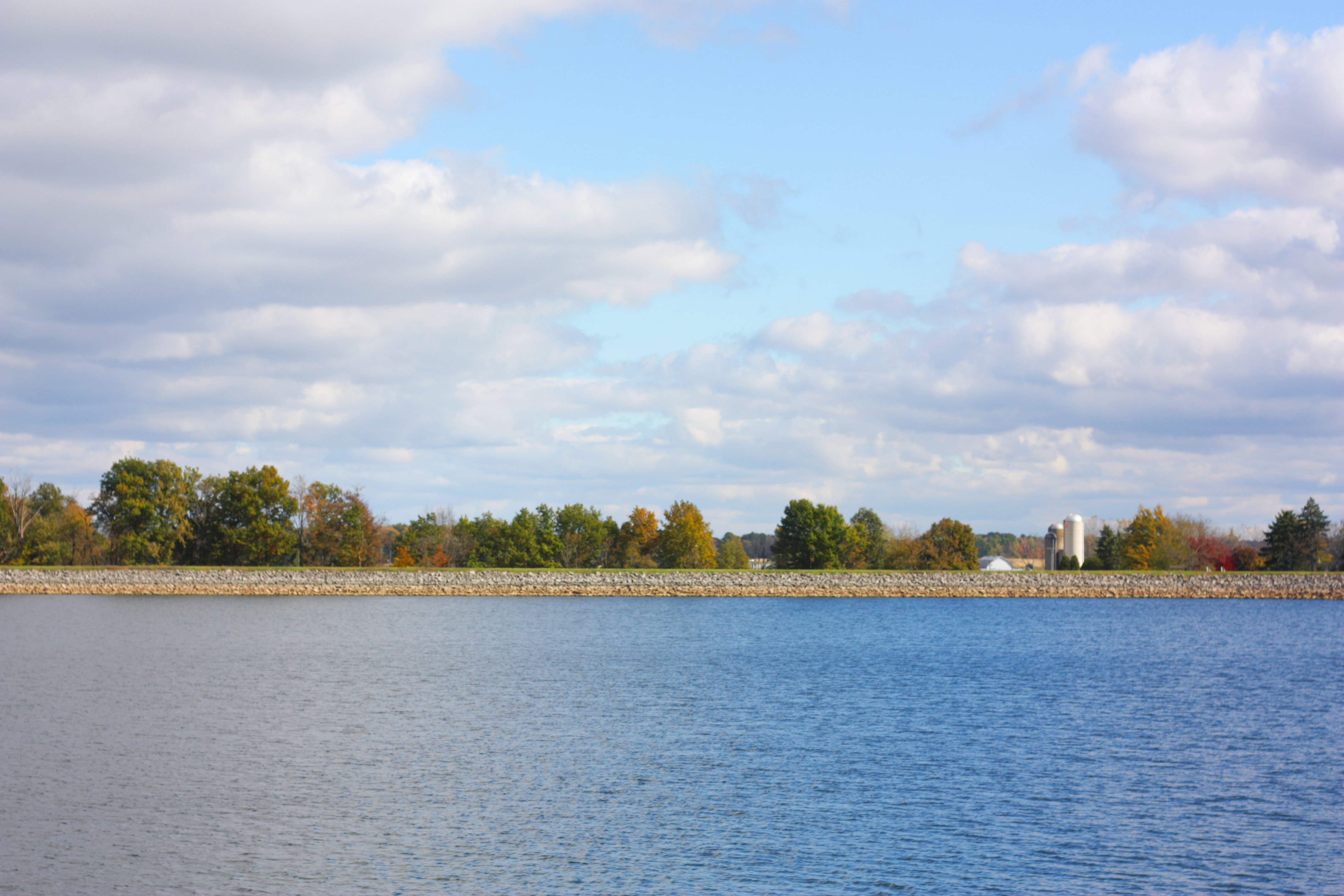 Blue lake with fall trees and a farm in the distance