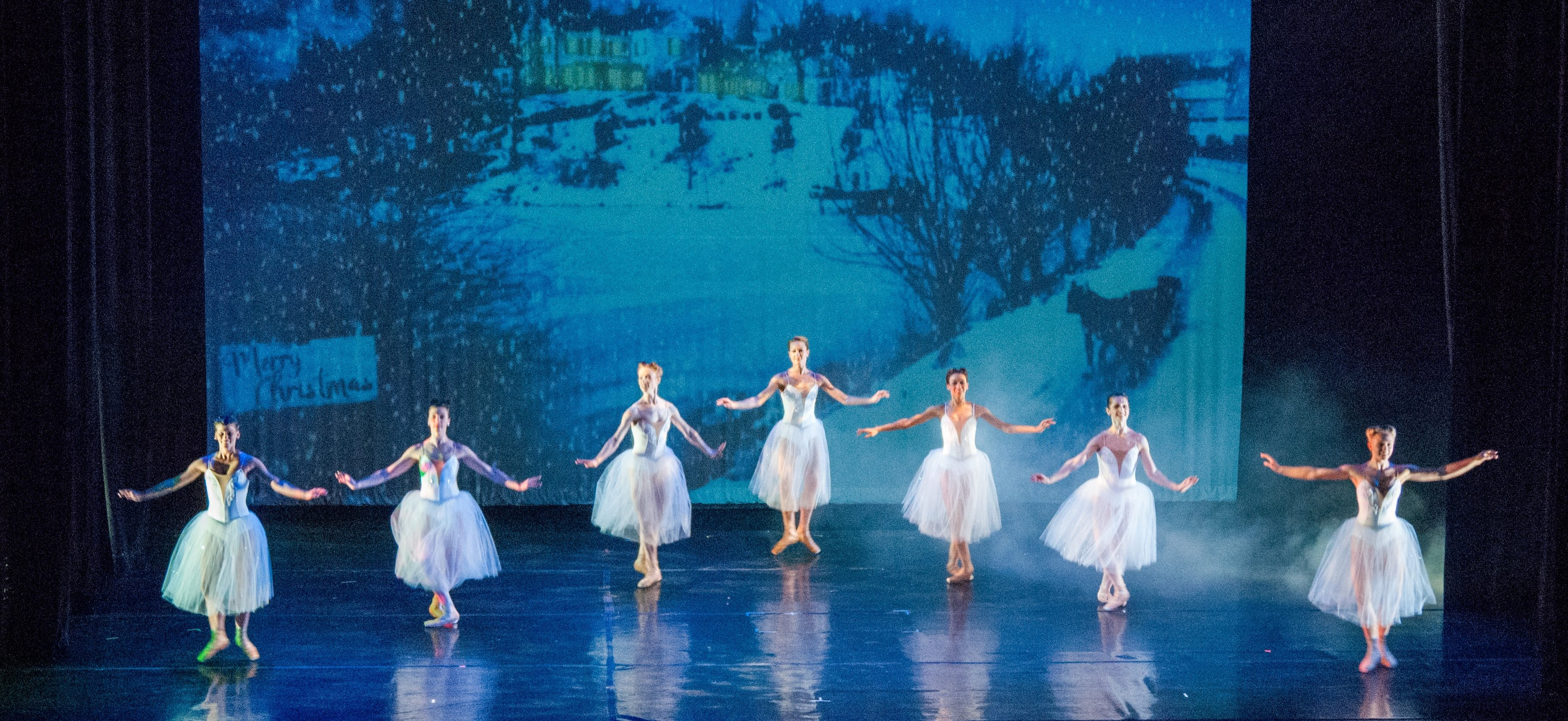 Seven ballerinas in white dresses dance in front of a blue backdrop