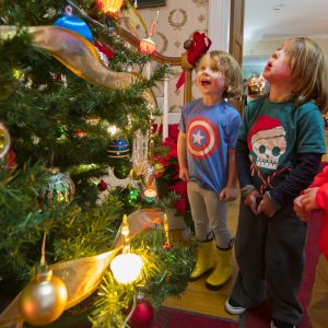 Three kids look at a Christmas tree in awe