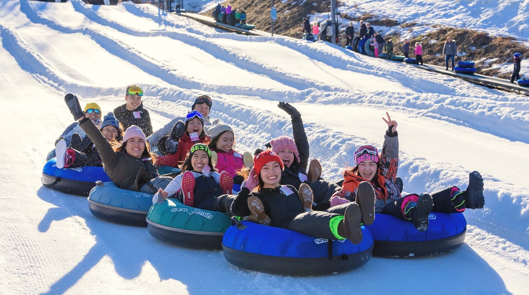 Group of people in snow tubes going down a snowy hill