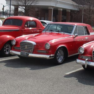 Shiny red Studebaker cars lined up in a parking lot